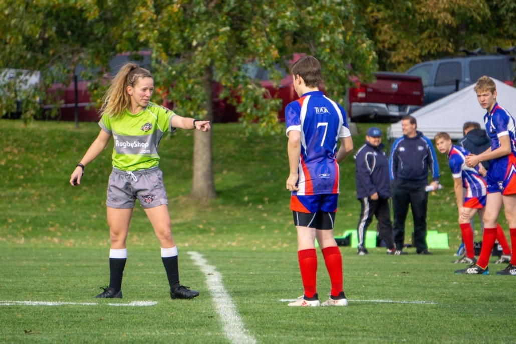 A referee talks to a player on the pitch