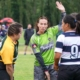 A referee talks to two players on the pitch